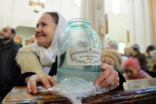 Бабушка держит бутыль с крещенской водой